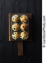 Homemade blueberry muffins on oak cutting board on black background with natural lighting top view