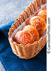 Homemade burger buns with sesame seeds in a basket.