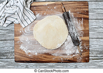 Homemade butter pie crust dough with rolling pin and towel over floured rustic wooden background. Image shot from overhead.