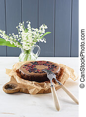 Homemade cake with bird cherry flour. Healthy Siberian dessert with bird cherry flour, cowberries and black currants served with lily of the valley bouquet and copy space