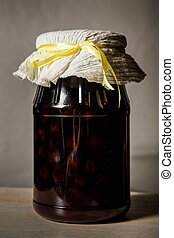 homemade canned cherries in glass jar on white table
