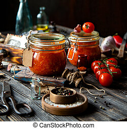 Homemade canned hot tomato sauce adjika in two glass jars standing on wooden board