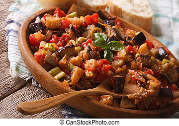 Homemade traditional Caponata with aubergines close-up on a wooden plate. horizontal