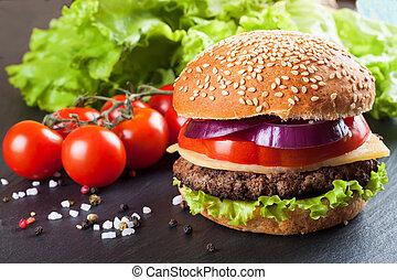 Homemade cheeseburger on black slate surface.