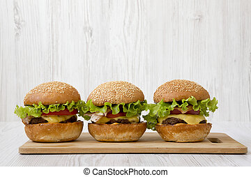 Homemade cheeseburgers on a bamboo board, side view. Close-up.