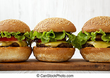Homemade cheeseburgers on rustic wooden board, side view. Close-up.
