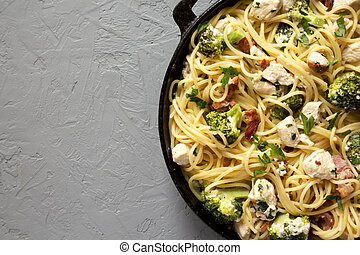 Homemade Chicken Bacon Broccoli Alfredo in a cast-iron pan on a gray surface, top view. Flat lay, overhead, from above. Space for text.