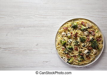 Homemade Chicken Bacon Broccoli Alfredo on a plate on a white wooden background, top view. Flat lay, overhead, from above. Space for text.