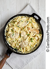 Homemade Chicken Fettuccine Alfredo in a cast-iron pan on a white wooden background, top view. Flat lay, overhead, from above. Close-up.