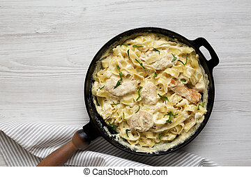 Homemade Chicken Fettuccine Alfredo in a cast-iron pan on a white wooden surface, top view. Flat lay, overhead, from above. Space for text.
