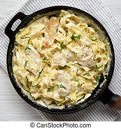 Homemade Chicken Fettuccine Alfredo in a cast-iron pan on a white wooden table, top view. Flat lay, overhead, from above. Close-up.