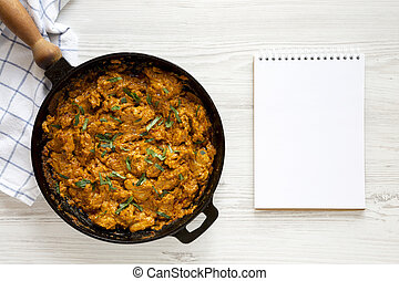 Homemade Chicken Tikka Masala in a cast iron pan, blank notepad on a white wooden surface, top view. Flat lay, overhead, from above. Space for text.
