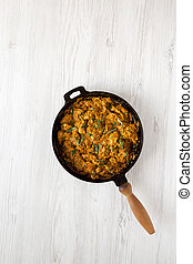 Homemade Chicken Tikka Masala in a cast iron pan on a white wooden background, top view. Flat lay, overhead, from above. Copy space.