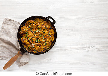 Homemade Chicken Tikka Masala in a cast iron pan on a white wooden table, top view. Flat lay, overhead, from above. Space for text.