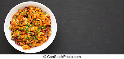 Homemade Chili Mac and Cheese with Parsley in a white bowl over black background, top view. Flat lay, overhead, from above. Space for text.