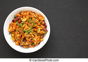 Homemade Chili Mac and Cheese with Parsley in a white bowl over black background, top view. Flat lay, overhead, from above. Copy space.