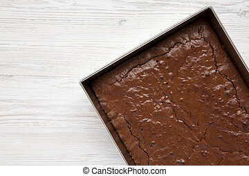Homemade chocolate brownie on a white wooden background, top view. Overhead, from above, flat lay. Space for text.