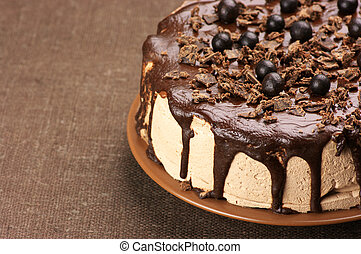Close-up of homemade chocolate cake on brown canvas.