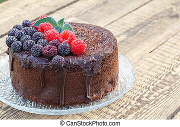 Homemade chocolate cake decorated with black and red raspberries on glass plate