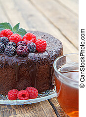 Homemade chocolate cake decorated with black and red raspberries on glass plate with cup of tea.