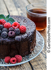 Homemade chocolate cake decorated with black and red raspberries on glass plate with cup of tea