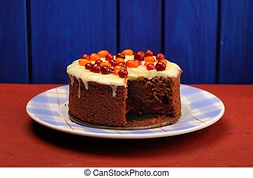 Homemade chocolate cake with fresh cranberries, sea-buckthorn and icing on wooden background
