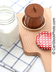 Homemade chocolate cake with glass of milk on wooden plate