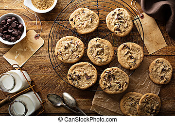Homemade chocolate chip cookies with milk on a cooling rack ...