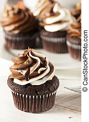 Homemade Chocolate Cupcake with chocolate frosting against a background