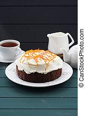 Homemade chocolate fruit cake with cream cheese and orange peel on dark blue background