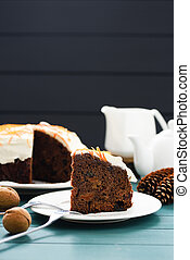 Homemade chocolate fruit cake with cream cheese icing and orange peel on blue background copyspace