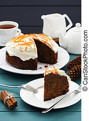 Homemade chocolate fruit cake with cream cheese icing and orange peel served with black tea on blue background