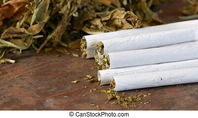 Homemade cigarettes or roll-up stuffed with tobacco are on a...