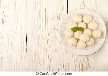 Homemade coconut candy on the white wooden background. Top view. Copy space. Selective focus