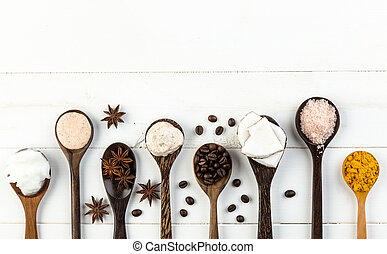 Homemade coconut products on white wooden table background. Oil, scrub, milk, lotion, himalayan salt, coffee beans, anise and turmeric from top view. Good for space and background