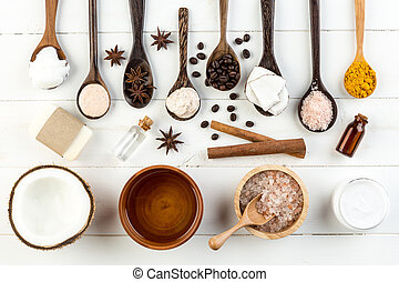 Homemade coconut products on white wooden table background. Oil, scrub, soap, milk, lotion, himalayan salt, coffee beans, anise, turmeric from top view. Good for space and background