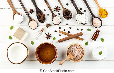 Homemade coconut products on white wooden table background. Oil, scrub, soap, milk, lotion, himalayan salt, coffee beans, anise, turmeric and mint from top view. Good for space and background