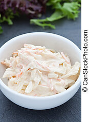 Homemade coleslaw in a white bowl on a slate background