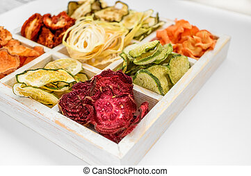 Homemade colorful chips from different fresh vegetables and carrots in a white wooden box on a white background. Close-up. Selective focus.