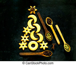 Homemade cookies and wooden spoons with spices on black background. The concept of celebration and cooking.