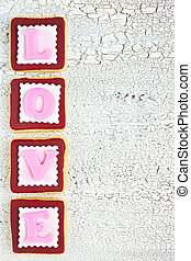 Homemade cookies creating word LOVE on white old wooden background, top view