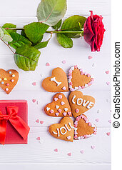 Homemade cookies in shape of heart with I Love you words as gift for lover on Valentine's day. White wooden table with greeting card, rose and decor. Festive gift concept. Selective focus. Copy space