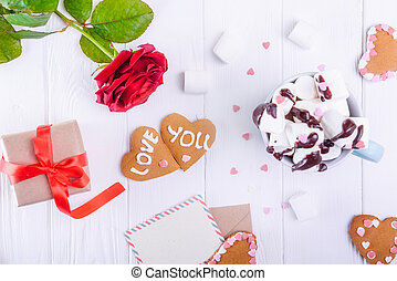 Homemade cookies in shape of heart with Love you lettering on the white wooden table with greeting card, flower, gift box and cup of cacao. Gift for lover on Valentine's day. Selective focus.