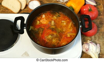 Vegetable or minestrone soup cook in a metal saucepan on the stove.