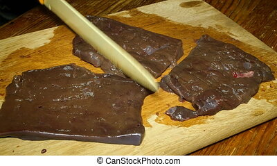Homemade cooking. Cooking liver steaks for frying. Chef softens raw beef liver and often beats it with a knife, on wooden cutting board.