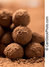Homemade cooking. Stack of appetizing black chocolate round truffles covered in cocoa dust. Shallow depth of field, close up