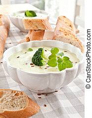 Homemade creamy broccoli soup and fresh baguette