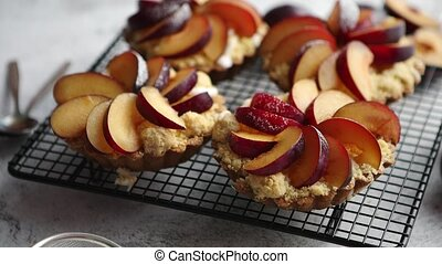 Homemade crumble tarts with fresh plum slices placed on iron...