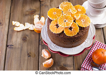 Homemade cupcake with tangerines on a white plate, for breakfast. wooden background, place for writing text.