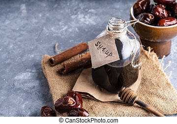 Homemade dates syrup in glass bottle on gray stone table. Alternative food and drink Trend food 2020. Copy space.